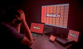 Somebody sitting at their desk in front of various devices that have been locked by WannaCry