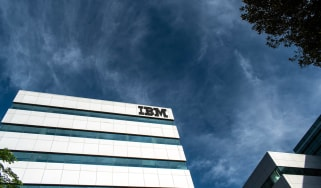 An IBM building as seen against a dark blue, cloudy sky