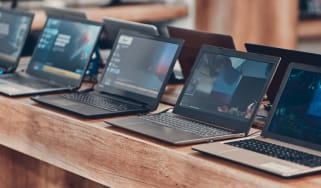 A row of laptops on a counter