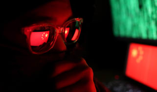 A hacker wearing glasses in a dark room with the Chinese flag shown in the background on a computer display