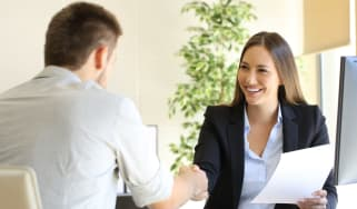 Two people at a job interview sat at a desk