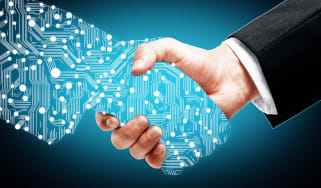 A hand made of technology shaking hands with a man in a suit