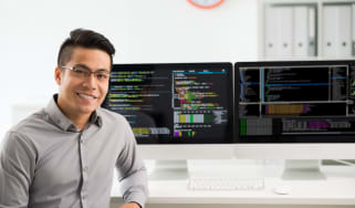 Man sitting in front of computer monitors with coding on them