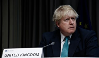 The prime minister, Boris Johnson, sitting on a panel in a dark room