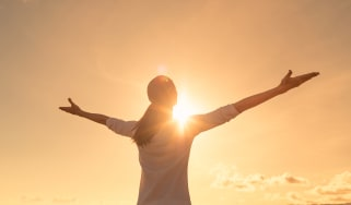 A woman standing in the sun with her arms outstretched and palms lifted up