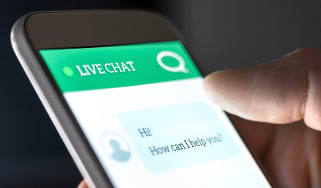 An unseen user interacting with a live chat feed displayed on a smartphone