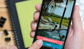 Hands holding an iPhone displaying the login page of the AirBnB app