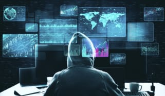 A hacker in a darkened room with digital maps and computer equipment