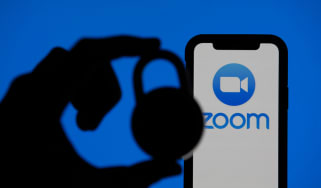 Zoom video conference app icon on a mobile device with silhouette of a padlock