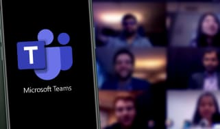 The Microsoft Teams logo on a smartphone in front of a Teams meeting