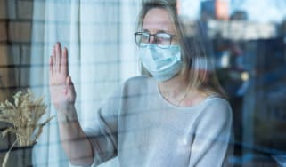 A woman in a facemask during the coronavirus crisis touching and looking out of a window