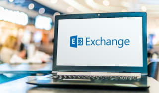 A laptop on a table with the Microsoft Exchange logo displayed