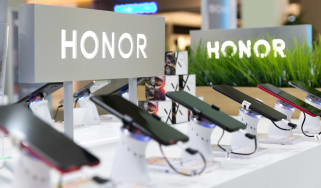 Honor smartphones shown on a retail display in an electronic store with the brand's logo in the background.