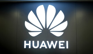 The Huawei logo glowing in a darkened room