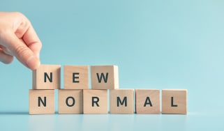 "Wooden blocks spelling out ""new normal"""