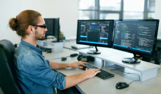 Man at a desk coding software