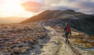 A woman with a red backpack walking along a hiking path towards the mountain summit of High Spy from Maiden Moor in the Lake District at sunrise