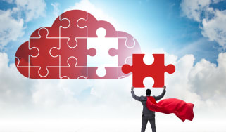A businessman wearing a red superhero cape lifting the final piece of a puzzle in the shape of a cloud into place