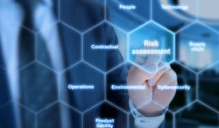 Man in suit in front of holographic display showing risk assessment and supply chain