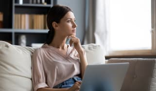 A young woman sitting on a sofa at home with a laptop on her lap looking thoughtfully into the distance