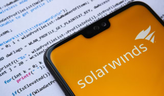 Solarwinds logo seen on the smartphone screen, with simple C attack code on the paper background.