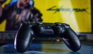 Cyberpunk 2077 game displayed on monitor behind a black PlayStation controller