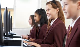 A group of schoolchildren working on PCs