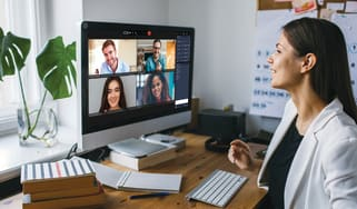 A women sits at her desk on a video call