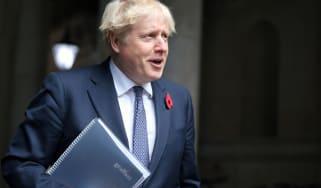 The prime minister, Boris Johnson, holding a folder