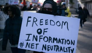 "Protestor holding sign reading ""Freedom of information, Net Neutrality"", at a rally for net neutrality on the streets of Philadelphia in January 2018."