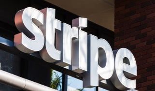 Stripe sign on a building with glass in the background