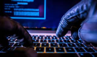 A hacker wearing black gloves using a laptop keyboard
