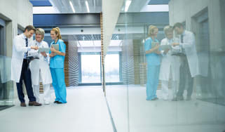 Three doctors in a hospital corridor cheerfully looking at some data on a tablet