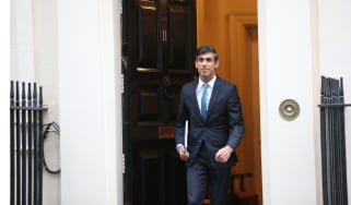 Chancellor Rishi Sunak walking through a door