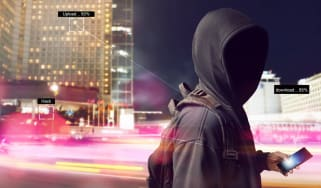 An anonymous hacker using smartphone on the street at night