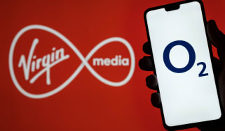 O2 Telefonica logo on smartphone screen hold in hand and Virgin Media logo on blurred background