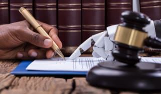 A photo of a person's hand signing a document with a robot's hand pointing at where to sign. There is a gavel in the foreground on the robot's side of the table.