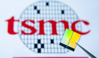 Chip held up with the TSMC sign in the background