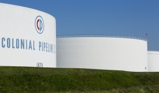 The Colonial Pipeline tanks situated on a green field with clear blue sky in background