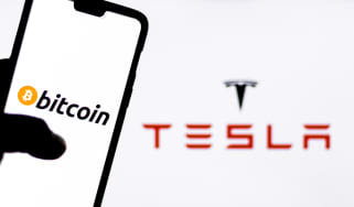 Somebody using a smartphone with Bitcoin on the face in front of a massive Tesla logo