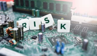 Four tiles spelling out risk on a computer circuit board