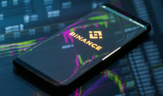Binance splash screen on a smartphone that's laying on a desk