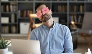 A man asleep at his desk with sticky notes over his eyes that have eyes drawn on them