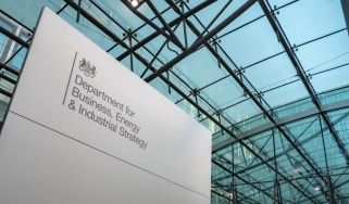 A governmental sign for the Department of Business, Energy & Industrial Strategy with glass ceiling in background