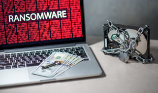 Money and keys resting on a laptop representing ransomware