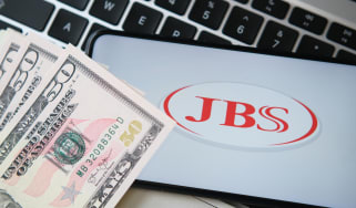 JBS meat producer logo seen on the smartphone screen with blurred money and laptop keyboard on the background