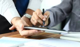 One person holds a tablet while another uses it to sign a contract