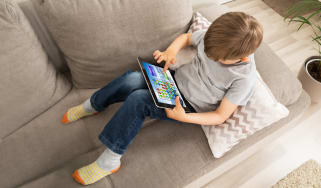 Kid sitting on a couch playing a tablet