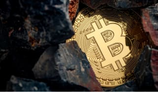 Abstract image of a bitcoin token inside some rocks to represent cryptocurrency mining