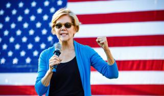 Senator Elizabeth Warren speaking in front of the US flag